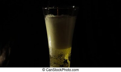 Pouring beer into a glass on a black background.
