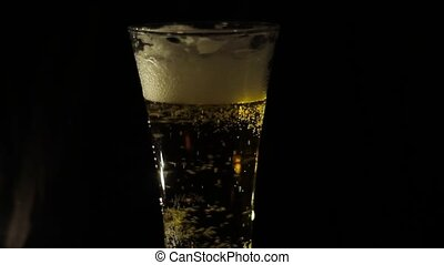 Pouring beer into a glass on a black background