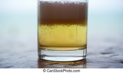 Pouring beer water in to glass with ice and froth - Pouring...