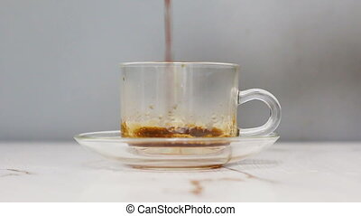Pouring black and hot coffee into a clear cup of coffee Close up shot