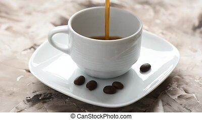Pouring black aromatic coffee into a white cup.