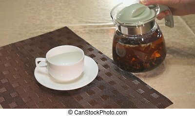 Pouring black tea in a white porcelain mug on a table