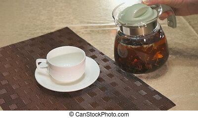 Pouring black tea in a white porcelain mug