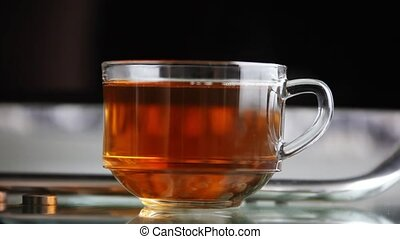 Pouring black tea in transparent glass and takes tea of hand.