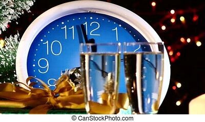 Pouring bubble champagne into glasses on New Year Eve against wall clock, bokeh, garland, on black