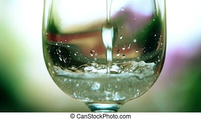 Pouring carbonated mineral water in a wineglass. Close-up slow motion shot