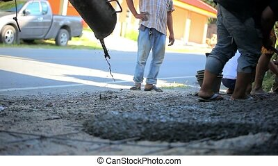 Pouring cement on the road and workers alignment it. Video...