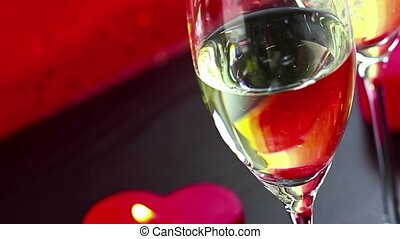 pouring champagne flutes near red candles burning, love and valentine day concept dolly camera movement