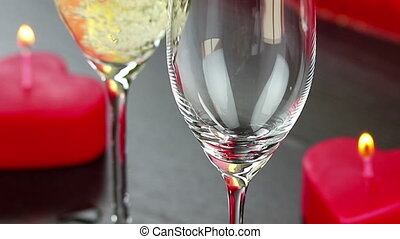 pouring champagne flutes near red candles burning, love and valentine day concept, dolly camera movement