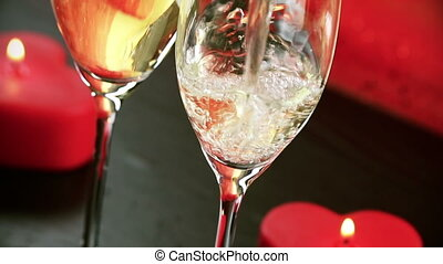 pouring champagne flutes with bubbles near red candles burning, love and valentine day concept