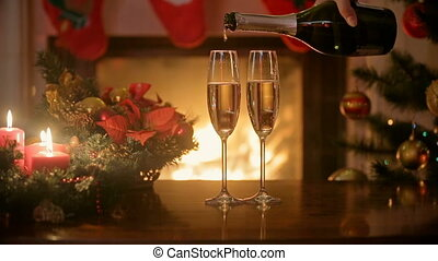 Pouring champagne in two glasses on Christmas dinner table. Burning fireplace at background