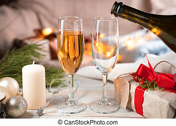 Pouring champagne into glasses on a Christmas background.