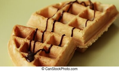 Fresh made belgian waffles, pouring chocolate flavored syrup to rich fluffy golden waffle, hot sweet melted chocolate topping, 4k