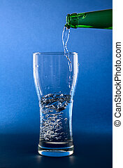 pouring clean water in glass on blue background