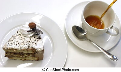 Composition of a slice of cake on a plate and a cup with coffee being poured into it. Good clip for restaurant or cafe, snack bar advertisement.
