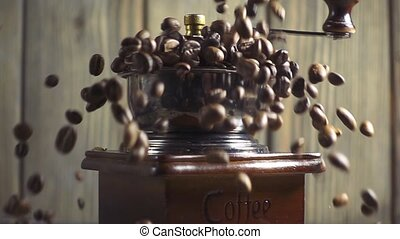 Pouring coffee beans into wooden vintage grinder, slow...