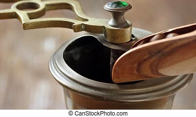 Pouring coffee beans to manual coffee grinder