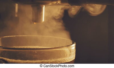 Pouring coffee from coffee machine in cup