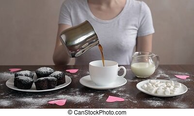 Pouring coffee from pot to cup - Woman pouring coffee from...