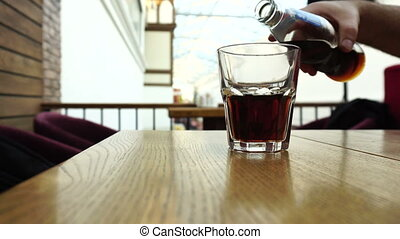 Pouring cola from the bottle into a glass - Pouring cola or...