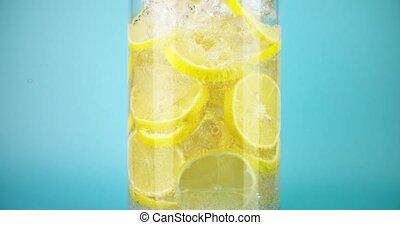 Pouring cold homemade lemonade into a glass, close-up slow ...