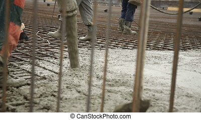 Pouring concrete mix from cement mixer on concreting...
