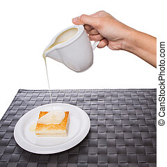 Female hand pouring condensed milk on a bread toast