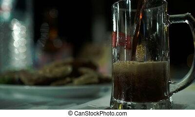Pouring dark beer into glass mug