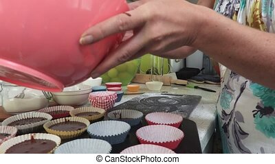 Pouring dough cake into muffin baking dish