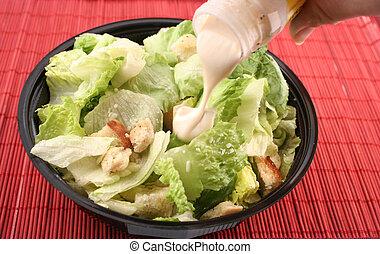 caesar salad - pouring dressing over lettuce for a caesar ...