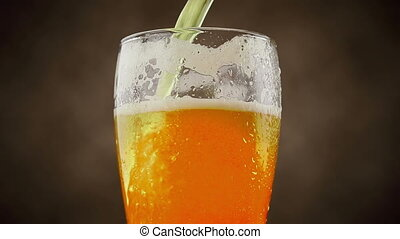 pouring fresh beer with foam into glass on brown background, zoom in movement camera