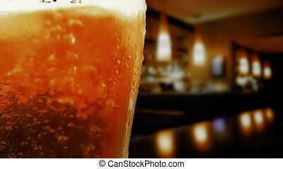 pouring fresh beer with foam into glass on table into pub background, zoom in movement camera