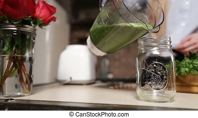 Pouring fresh green smoothie from blender into jar