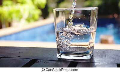 Pouring fresh water in a glass near swimming pool. Slow Motion.