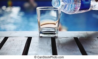 Pouring fresh water in a glass standing on wooden table near...