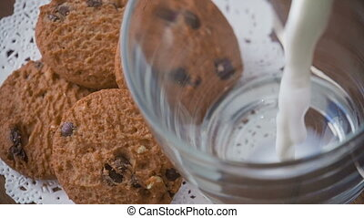 Pouring glass of milk and cookies, slow motion