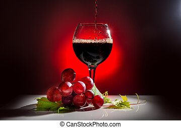 pouring glass of red wine and grapevine with green leaf