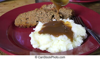Pouring gravy on potatoes - Spooning brown gravy onto mashed...