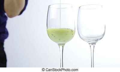 pouring green detox smoothie into a glass. healthy eating...