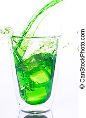 pouring green water in to clear glass