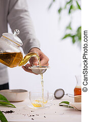 Pouring healthy tea. Hot tea on a glass teapot on a wooden table.