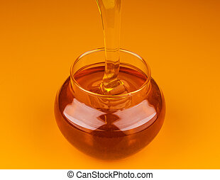 Pouring honey isolated on yellow background