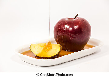 Pouring honey on red apple and red apple slice on white...