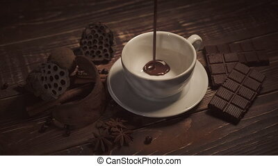 pouring hot chocolate with anise and cinnamon sticks on dark wooden table