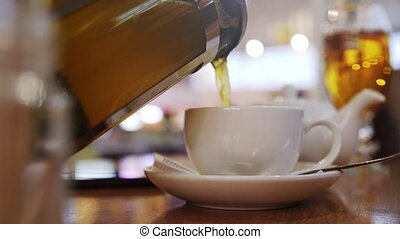 Pouring hot tea into the beautiful english tea cup in breakfast cafe. slow motion
