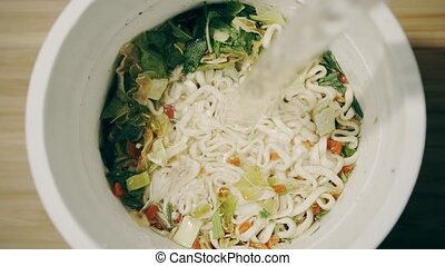 Pouring hot water into cup with instant noodles, top down...
