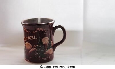 Pouring hot water into the mug, white background