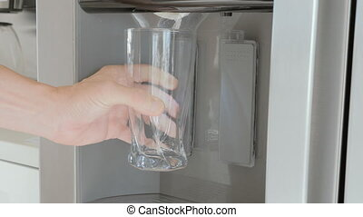 pouring ice cubes from a fridge door into a glass