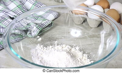 Pouring ingredients into a mixing bowl - Pouring baking mix...