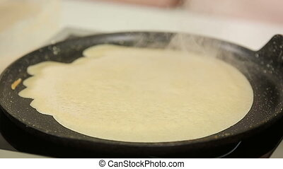 Pouring liquid dough on a hot pan while frying pancakes